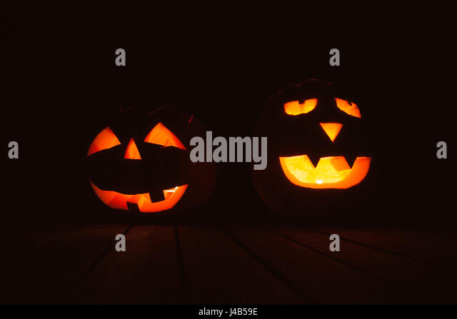 Halloween pumpkin lanterns with evil faces in the dark with light at a halloween festival - Stock Image