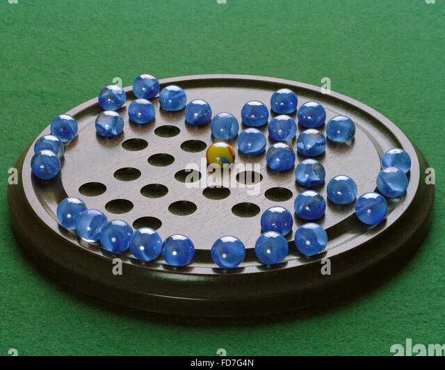 Fox and Geese marbles board game on green baize - Stock Image