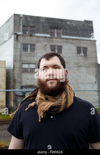 Young adult man outdoors in an urban environment for a lifestyle portrait of a bearded hipster. - Stock-Bilder