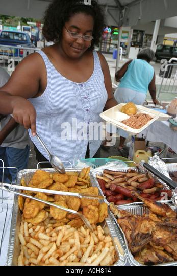 Coconut Grove Florida Grand Avenue Bahamas Goombay Festival Black woman prepares ethnic food vendor - Stock Image