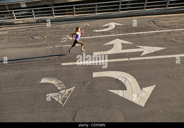 Female runner running on urban city street bridge, overpass with directional arrows painted on pavement - Stock-Bilder