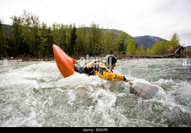 A playboater enjoys a small wave on a river. - Stock-Bilder