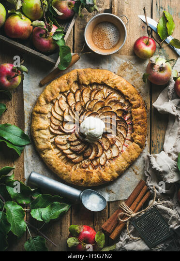 Homemade apple crostata with cinnamon, ice-cream scoop and fresh apples - Stock Image