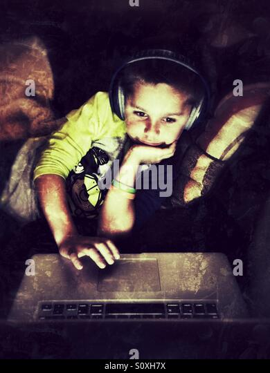Young boy with headphones uses a laptop - Stock-Bilder