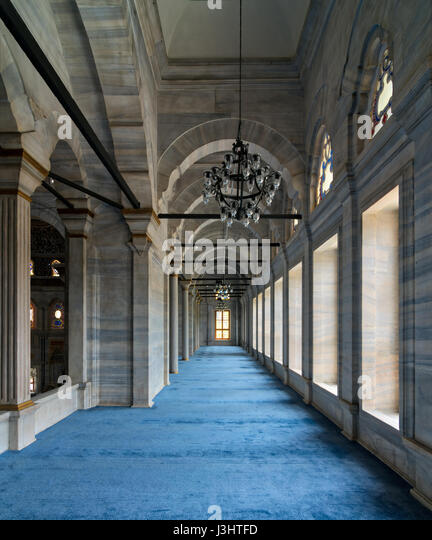 Passage in Nuruosmaniye Mosque, a public Ottoman Baroque style mosque, with columns, arches and floor covered with - Stock Image