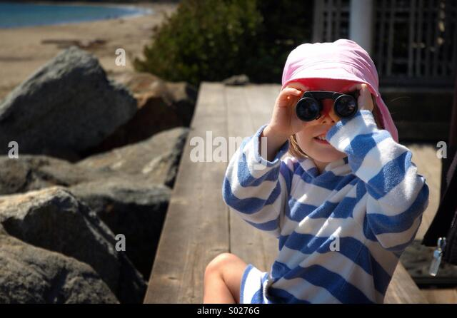 Little girl looks through binoculars. - Stock Image