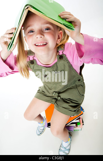 Image of pretty young girl under book in the studio - Stock Image