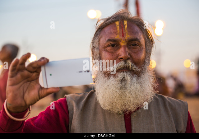Hindu pilgrim taking a picture with his smartphone at the Kumbh Mela, Allahabad, India - Stock Image
