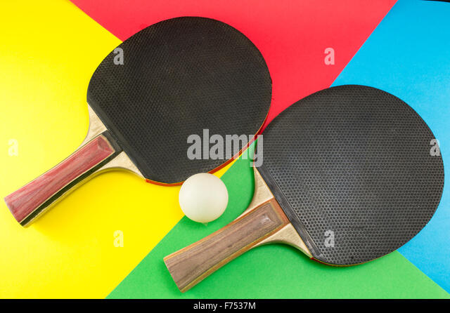 Pair of table tennis paddles on a colorful collage background - Stock Image
