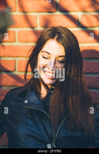 Young beautiful brunette portrait, warm sunset light and shadow pattern created by tree branch - Stock Image
