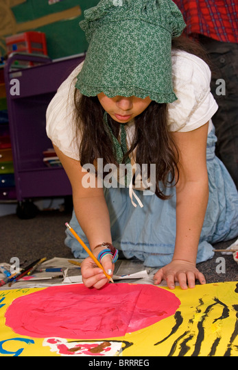 Young girl paints poster in elementary school while wearing a period costume as part of school project - Stock-Bilder