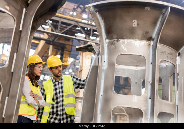 Steel workers examining part in factory - Stock Image
