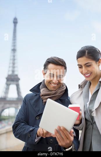 Business people using digital tablet near Eiffel Tower, Paris, France - Stock Image