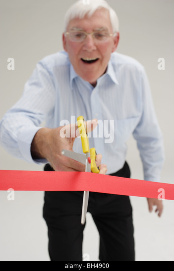 Senior businessman about to cut through a red tape, laughing - Stock-Bilder