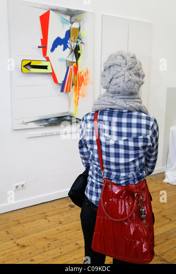 Young woman with a wool cap looking at the abstract painting of an art student, tour Kunstakademie Art Academy in - Stock Image