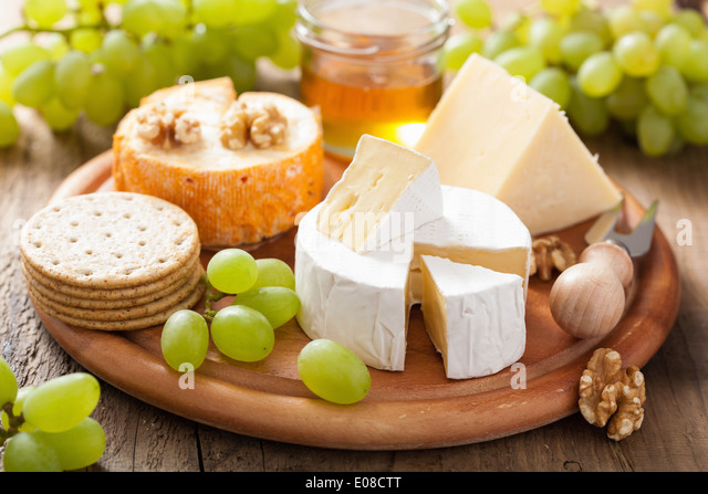 cheese plate with camembert, cheddar, grapes and honey - Stock Image
