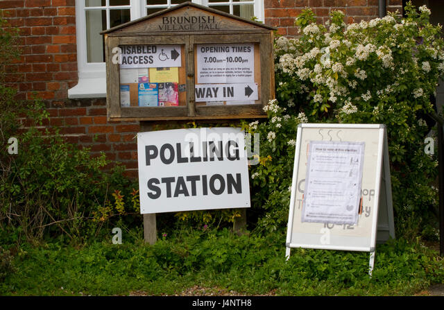 Polling station sign by a village noticeboard - Stock Image