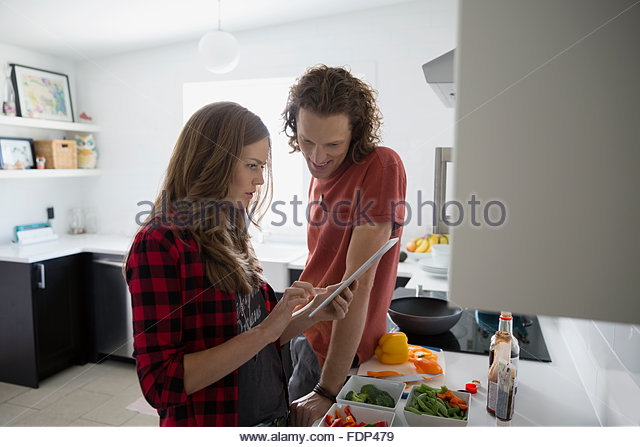 Couple with digital tablet cooking in kitchen - Stock Image