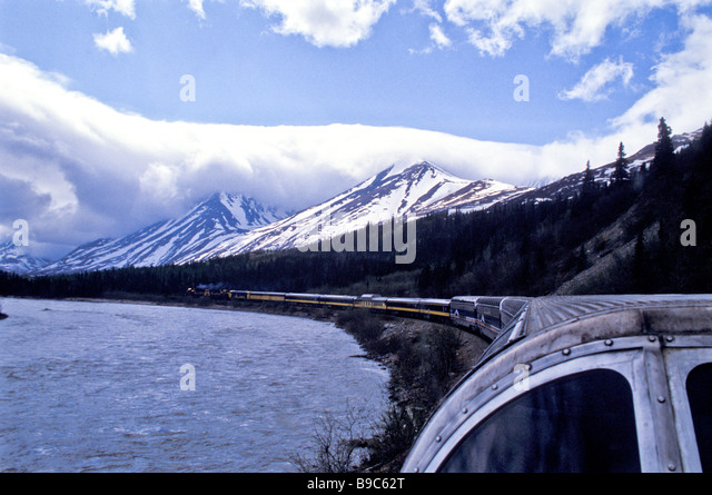 Alaska cruise tour train ride to Denali passing beside lake long string of cars low white clouds on horizon - Stock Image