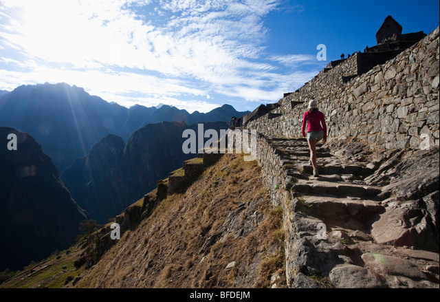 A teenager walks up an ancient staircase overlooking a steep valley as she visits the site of a lost civilization. - Stock Image
