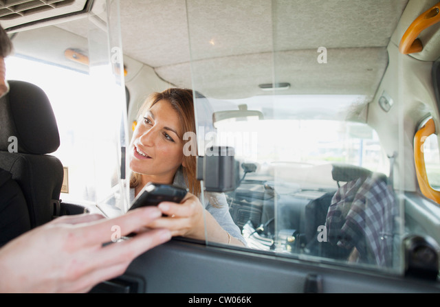 Woman handing cell phone to taxi driver - Stock Image