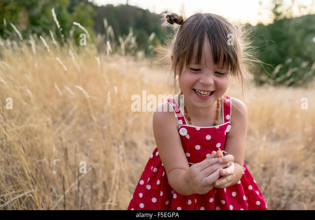 Laughing girl sitting in a field - Stock Image