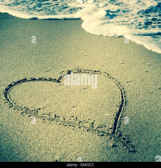 A heart drawn in the sand at the shoreline. Manhattan Beach, California USA. - Stock-Bilder
