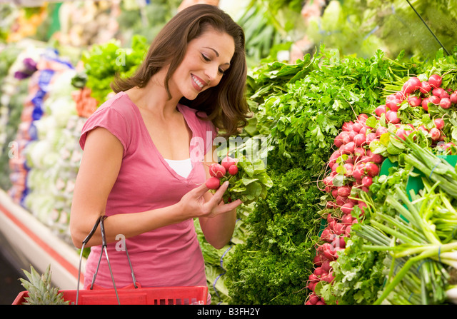 Woman shopping for beets at a grocery store - Stock Image