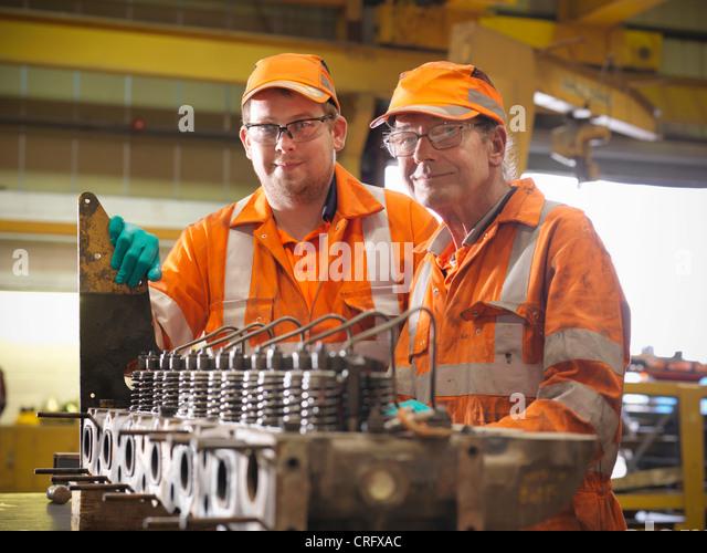 Engineer teaching apprentice in factory - Stock-Bilder