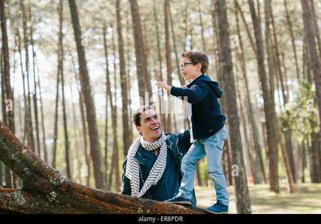Happy father assisting son in climbing tree at forest - Stock Image