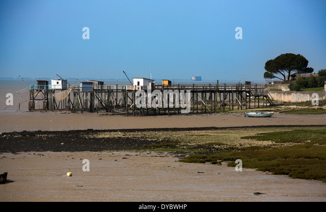 Tide out revealing sea bed and wrecked pier - Stock Image