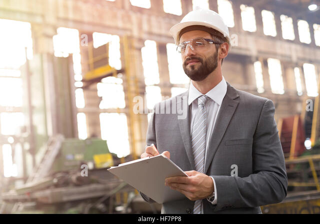 Manager with clipboard in steel factory - Stock Image