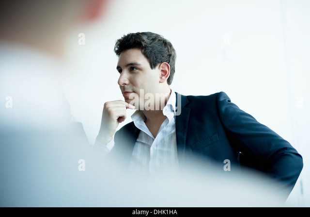 Young businessman listening in a business meeting - Stock Image