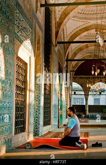 Man praying in Rustem Pasha Mosque. Istanul, Turkey. - Stock Image
