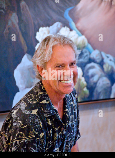 Talented and noted artist Doug West stands before one of his works at his gallery in Arroyo Seco, New Mexico. - Stock Image