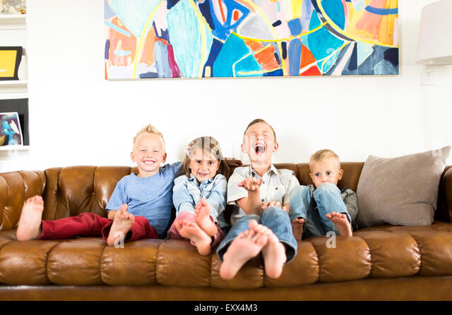 Smiling children (2-3, 4-5, 6-7) sitting on sofa - Stock Image