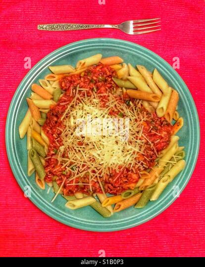 Penne alla Putanesca. A turquoise colored dinner plate sits on a bright red tablecloth, containing colorful penne - Stock-Bilder