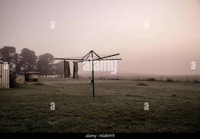 towels hang from a clothesline in foggy mist in dawn - Stock Image