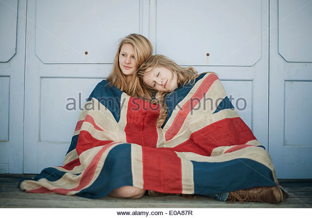 Portrait of sisters sitting on porch wrapped in union jack flag - Stock Image