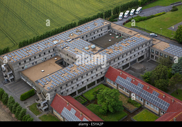 Photovoltaic solar panels on roof providing electricity by sun energy to office buildings - Stock Image