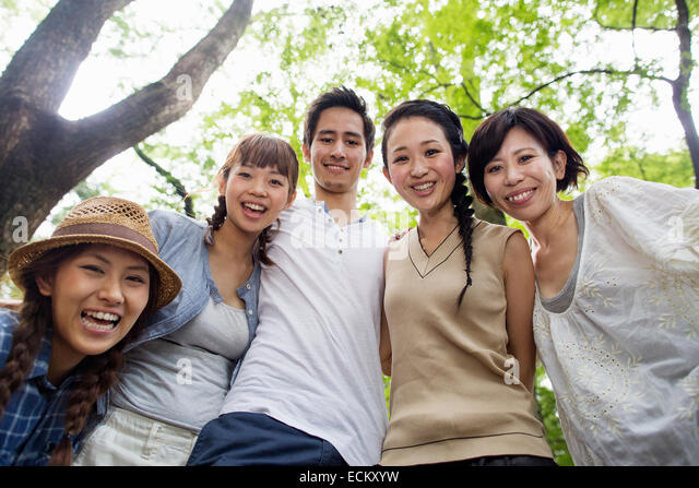 Group of friends at an outdoor party in a forest. - Stock Image