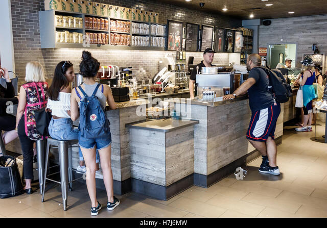 New York New York City NYC Manhattan Upper East Side Starbucks Coffee customers counter man woman barista cashier - Stock Image