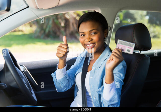 cheerful African girl holding her driver's license she just got - Stock Image