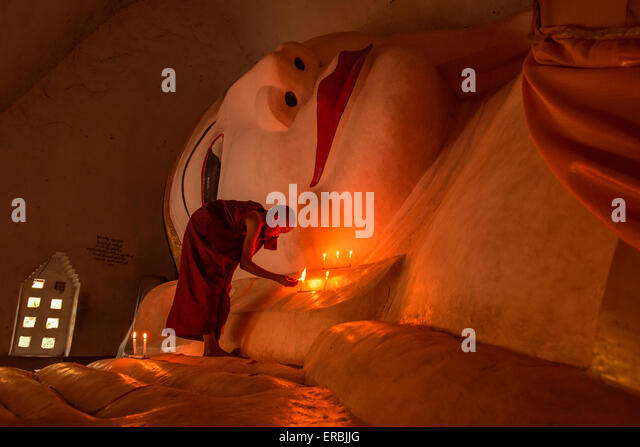 Monk lighting candles at reclining Buddha in Mandalay Myanmar - Stock-Bilder
