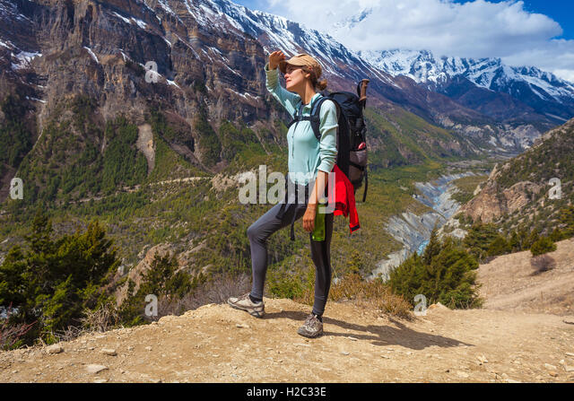 Beautiful Woman Traveler Backpacker Mountains Path.Young Girl Looking Top Hill and Take Rest.North Summer Snow Landscape - Stock Image