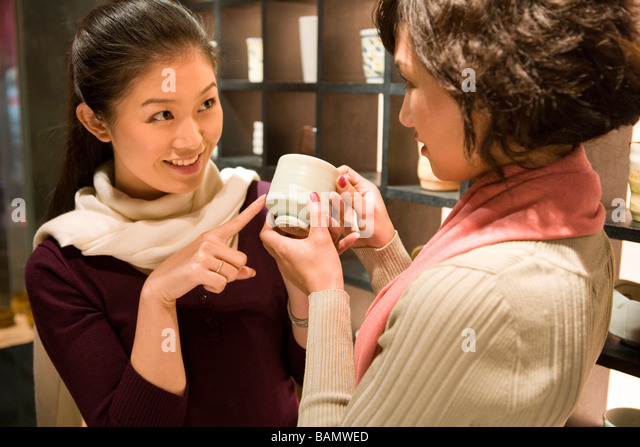 Two Young Women Looking At Objects In Shop - Stock Image