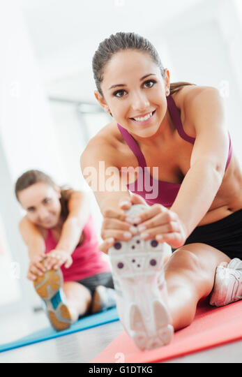 Smiling young women at the gym doing a stretching exercise for legs on a mat, fitness and health concept - Stock-Bilder