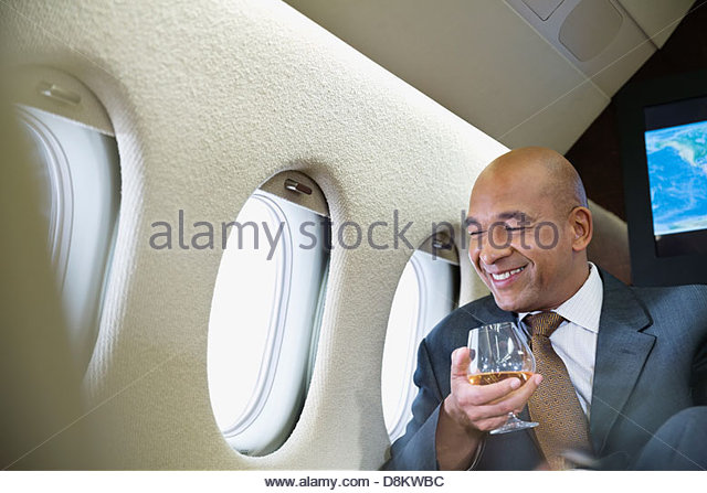 Businessman relaxing with a drink in private jet - Stock Image