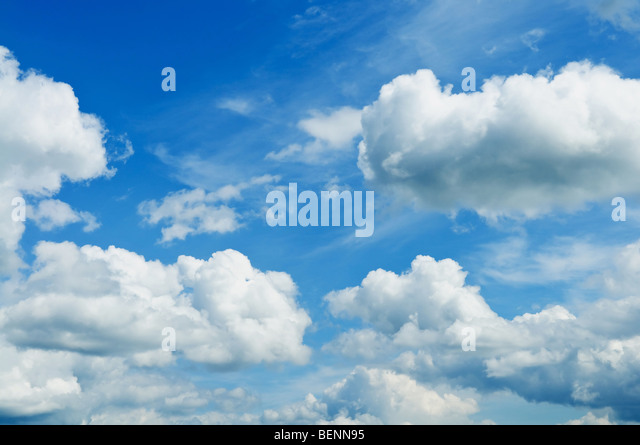 White cumulus clouds and a blue sky. - Stock Image