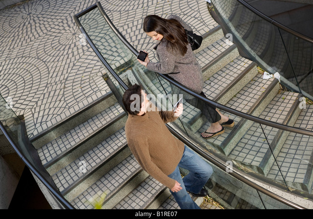 A young man and woman are passing each other on a stairwell carrying hand held computerized devices. - Stock Image